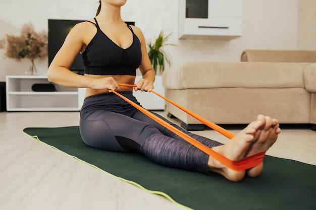Kobieta robi ćwiczenia z taśmami oporowymi w domu. przycięte ujęcie młodej kobiety ćwiczącej z gumką na podłodze.