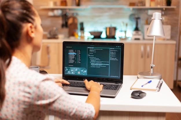 Kobieta robi cyberprzestępczą działalność hacking firewall za pomocą laptopa z domowego biura w nocy. programista piszący niebezpieczne złośliwe oprogramowanie do cyberataków przy użyciu wydajnego laptopa o północy