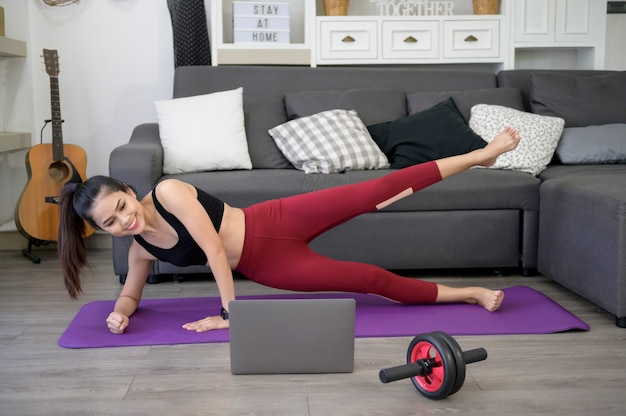 Kobieta robi deskę do jogi i ogląda samouczki szkoleniowe online na swoim laptopie w salonie