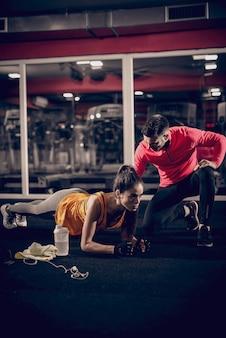 Kobieta robi deski i jej osobisty trener klęczy obok niej. oświetlenie boczne, wnętrze siłowni.