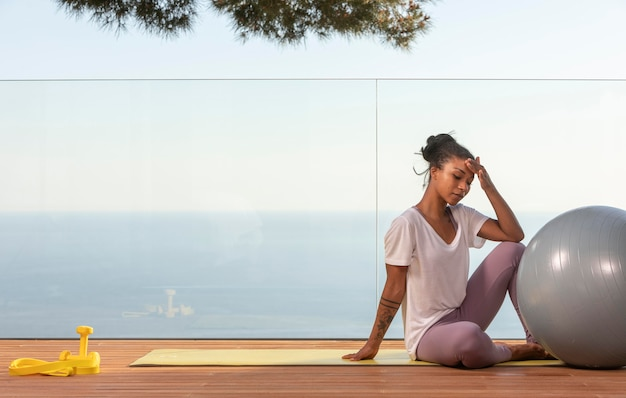 Kobieta robi fitness w domu na balkonie