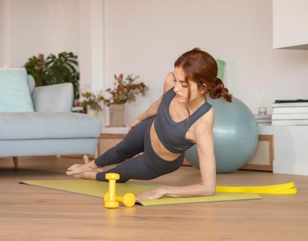 Kobieta robi fitness w domu na macie