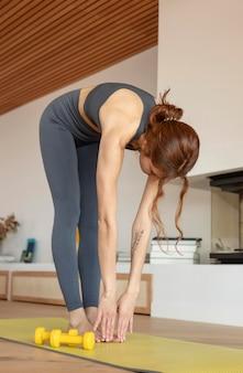 Kobieta robi fitness w domu z ciężarami