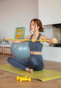 Kobieta robi fitness w domu z zespołem