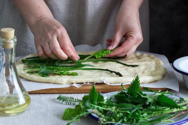 Kobieta robi focaccia z ciasta drożdżowego z różnymi ziołami. styl rustykalny.