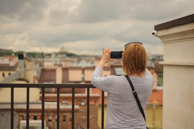 Kobieta robi fotografii widok na budynkach pod chmurnym niebem
