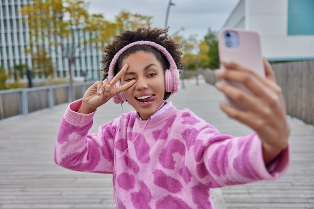 Kobieta robi gest pokoju nad okiem wystaje język robi selfie portret na telefonie ma słuchawki na uszach ubrany w swobodny sweter pozuje na zewnątrz