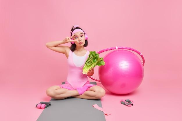 Kobieta robi gest pokoju siedzi skrzyżowane nogi na macie trzyma świeże zielone warzywa słucha muzyki ma aerobik trening otoczony bu fitball hula hop sprzęt sportowy.