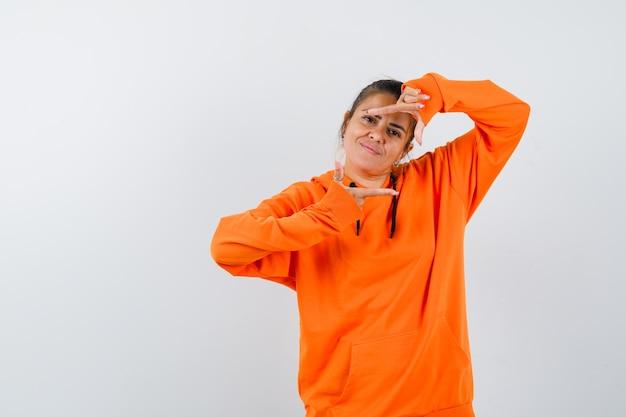 Kobieta robi gest ramki w pomarańczowej bluzie z kapturem i wygląda wesoło