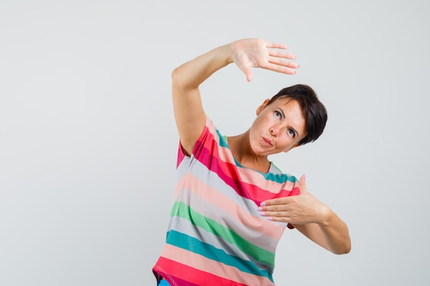 Kobieta robi gest ramy w pasiastej koszulce i patrząc ostrożnie