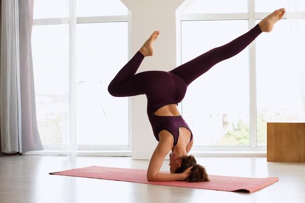 Kobieta robi head head asana. kombinezon do jogi. międzynarodowy dzień jogi