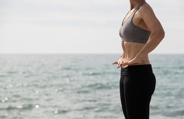 Kobieta robi hypopressive ćwiczeniu w morzu