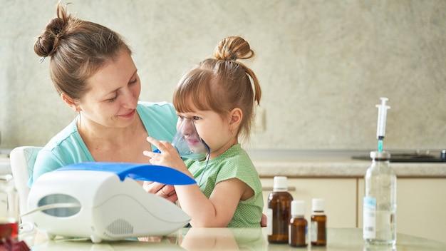 Kobieta robi inhalację dziecku w domu. zbliża maskę nebulizatora do twarzy. wdycha opary leku. dziewczyna oddycha przez maskę. medycyna na stole.