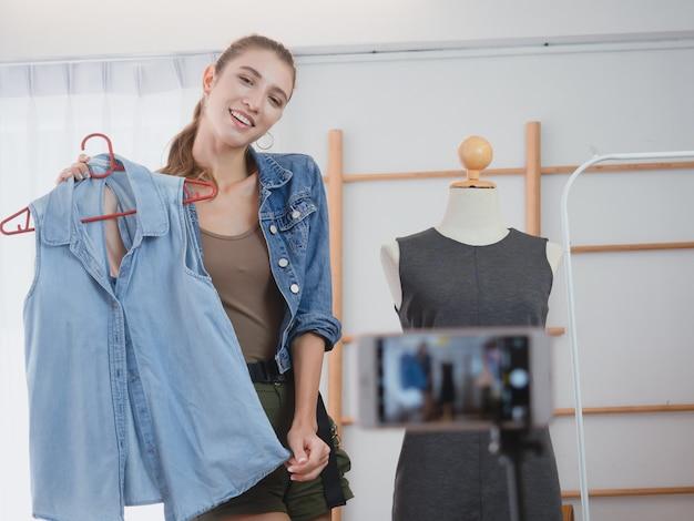 Kobieta robi interesy w swoim domu, kobiety oferują ubrania na sprzedaż online