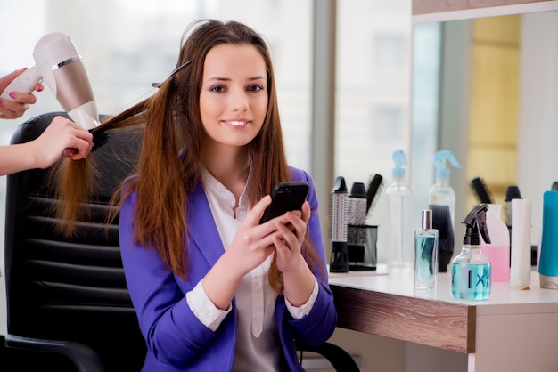 Kobieta robi jej włosy robić w piękno sklepie