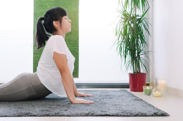 Kobieta robi jodę dla dobrego samopoczucia z rękami na podłodze przed oknem