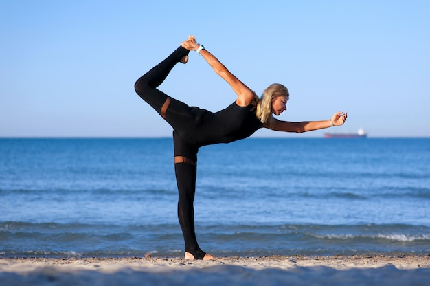 Kobieta robi joga asana przy plażą