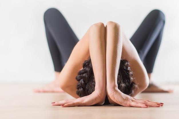 Kobieta robi joga leżąc na podłodze w artystycznej postawie estetycznej.