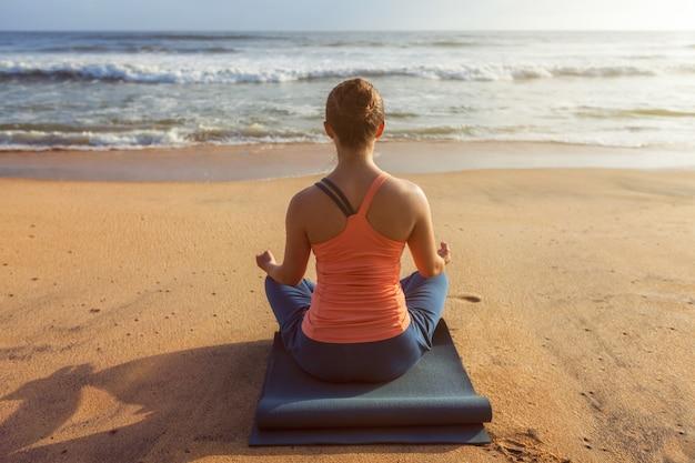 Kobieta robi joga lotos pozuje oudoors przy plażą