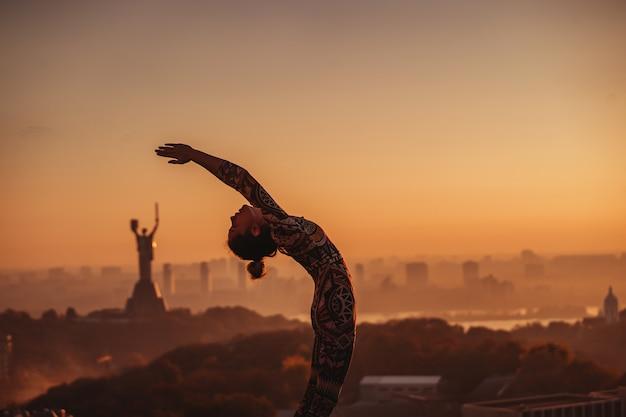Kobieta robi joga na dachu drapacza chmur w dużym mieście.