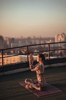 Kobieta robi joga na dachu drapacza chmur w dużym mieście