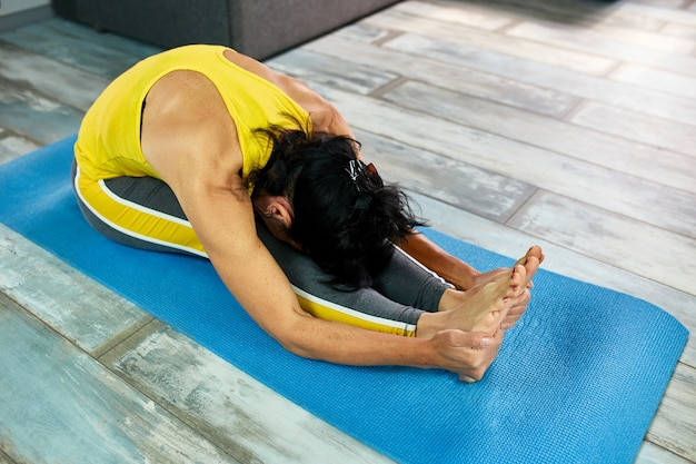 Kobieta robi joga w domu, robi ćwiczenia rozciągające.