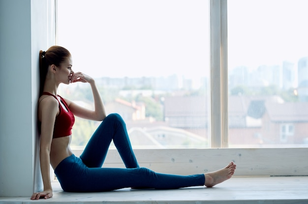 Kobieta robi joga w pobliżu okna relaksacyjnego medytacji stylu życia