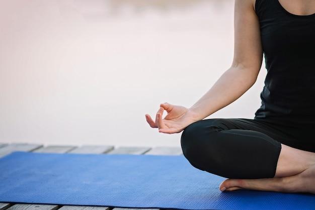 Kobieta robi joga w pozycji lotosu na zewnątrz w pobliżu rzeki na drewnianym molo w godzinach porannych
