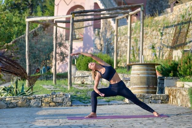 Kobieta robi joga z wydłużonym kątem bocznym, rozciągając i ujędrniając mięśnie tułowia na świeżym powietrzu w ogrodzie