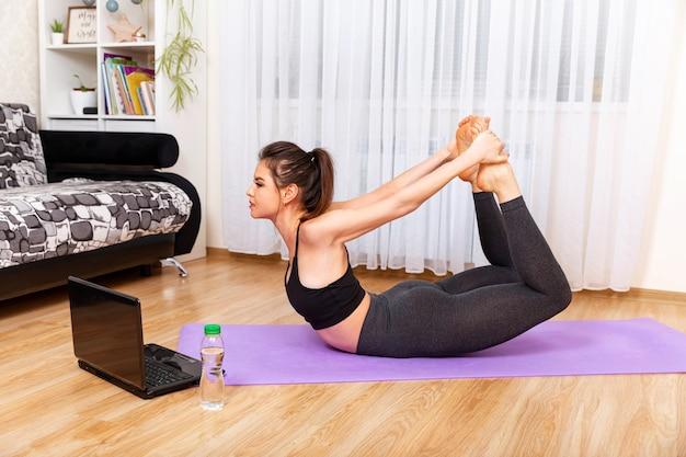 Kobieta robi jogę i ogląda zajęcia online w domu