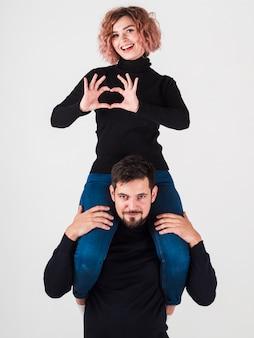 Kobieta robi kierowemu kształtowi z rękami na górze mężczyzna
