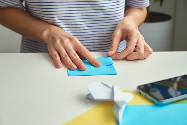 Kobieta robi królika wielkanocnego origami z kolorowego papieru
