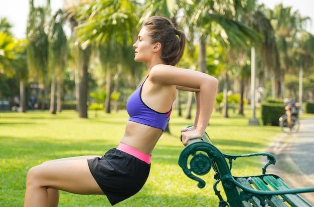 Kobieta robi ławce pompki do triceps w parku