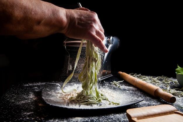 Kobieta robi makaronowi w talerzu z kuchni narzędziami na czarnym tle. poziomy widok z boku