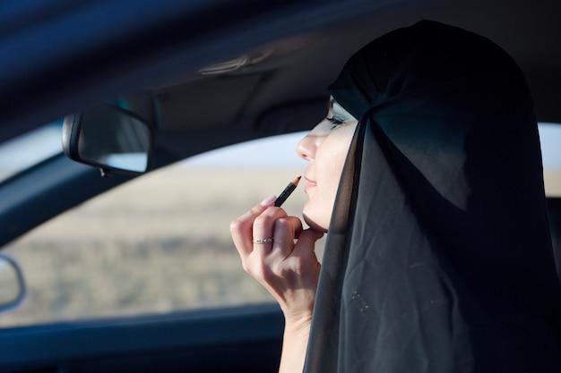 Kobieta robi makijaż w samochodzie spóźniona do pracy.,