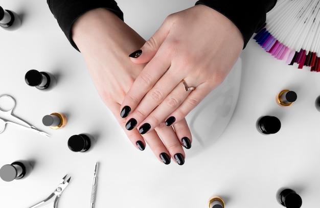 Kobieta robi manicure'owi w piękno salonie.