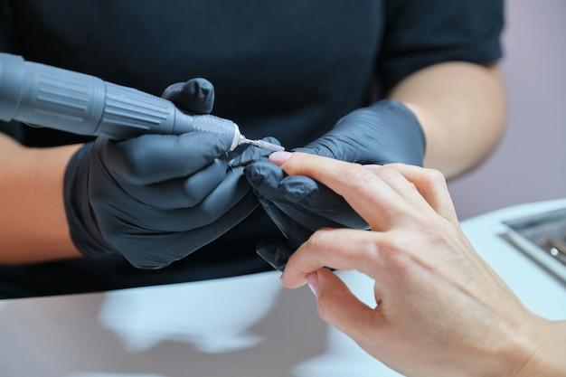Kobieta robi manicure w salonie do pielęgnacji rąk i paznokci