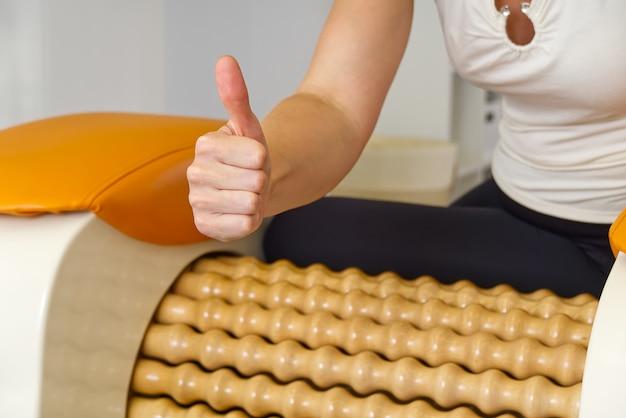 Kobieta robi masaż kości udowej nogi.