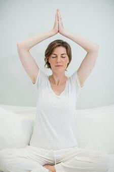 Kobieta robi medytacji na łóżku w sypialni