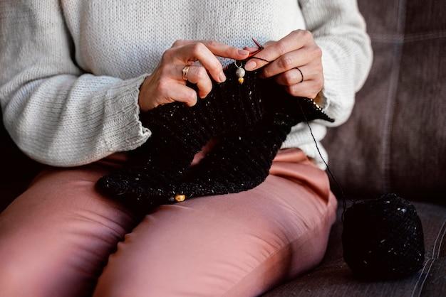 Kobieta robi na drutach czarną nitkę