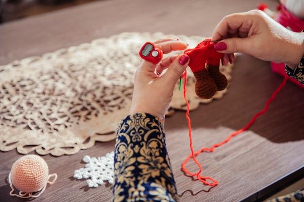 Kobieta robi na drutach figury z czerwoną nicią