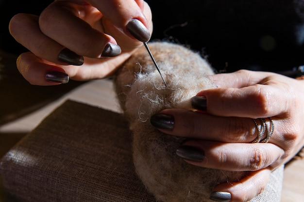 Kobieta robi na drutach rzeczy z wełny
