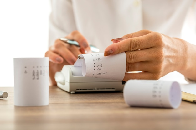 Kobieta robi obliczenia na maszynie sumującej lub kalkulatorze wyciągającym ryzy papieru z wydrukowanymi liczbami i sumami, konceptualne księgowanie księgowości, zbliżenie jej rąk.