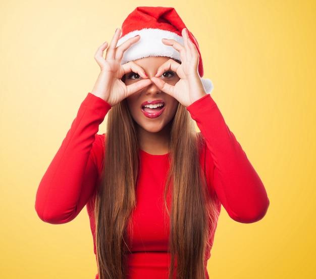 Kobieta robi okulary palec w żółtym tle