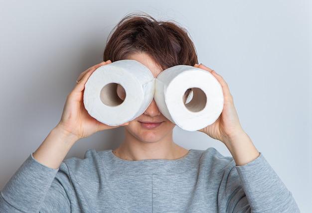 Kobieta robi okulary z rolek papieru toaletowego. podniecenie, panika, dewastacja sklepów. studio fotografii, na białym tle.