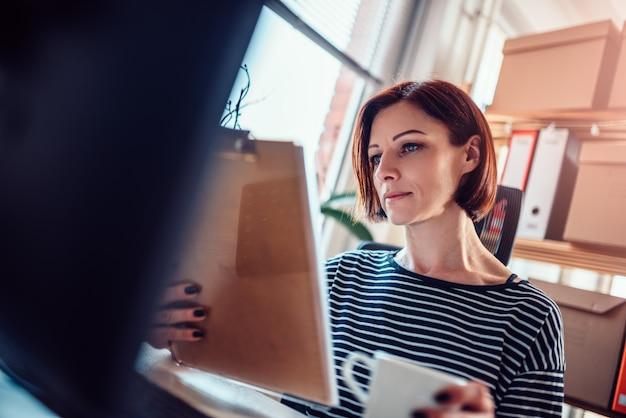 Kobieta robi papierkowej robocie przy biurem