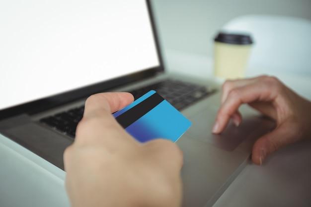 Kobieta robi płatności online za pomocą laptopa i karty kredytowej