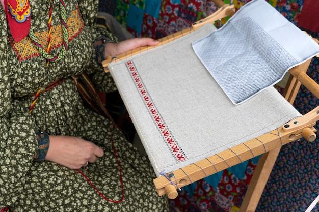 Kobieta robi płótno na starym krośnie. festiwal rekonstrukcji historycznej. proces tkania odzieży.