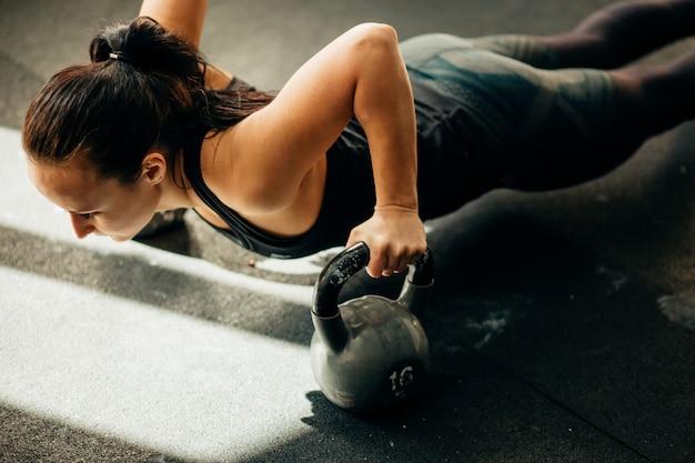 Kobieta robi pompki ćwiczenia na kettlebells. trening cross fit