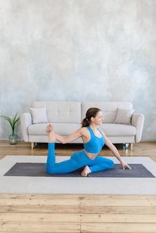 Kobieta robi poranne ćwiczenia jogi w domu na macie